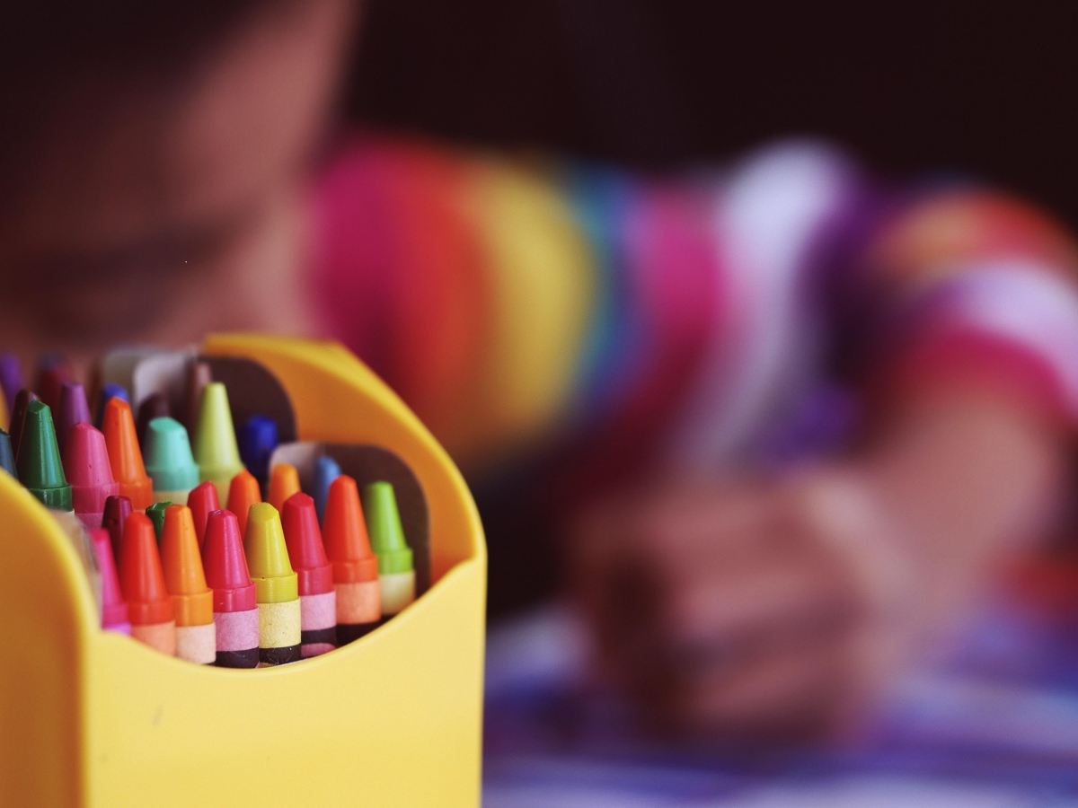 Crayons beside child coloring